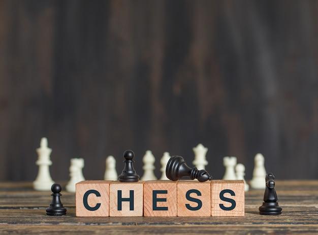 Concetto di strategia aziendale con i pezzi degli scacchi sui cubi di legno sulla vista laterale della tavola di legno.