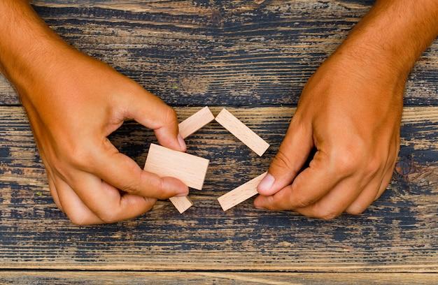 Concetto di strategia aziendale sulla disposizione di legno del piano del fondo. mano che tiene blocchi di legno.