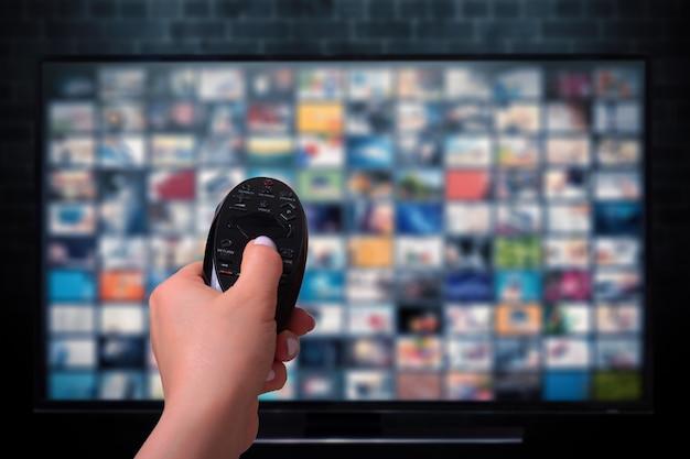 Concetto di streaming multimediale. mano che tiene il telecomando. schermo tv con molte immagini.