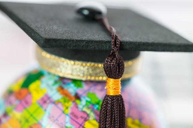 Concetto di studio laureato all'estero, tappo di laurea in cima mappa del modello di globo terrestre