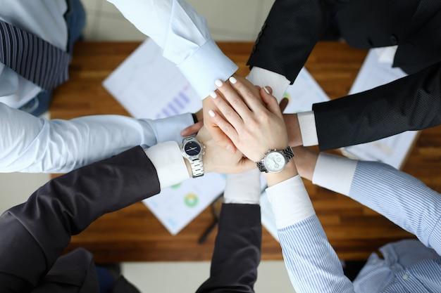 Concetto di successo aziendale. la gente del gruppo che tiene insieme alto vicino della mano