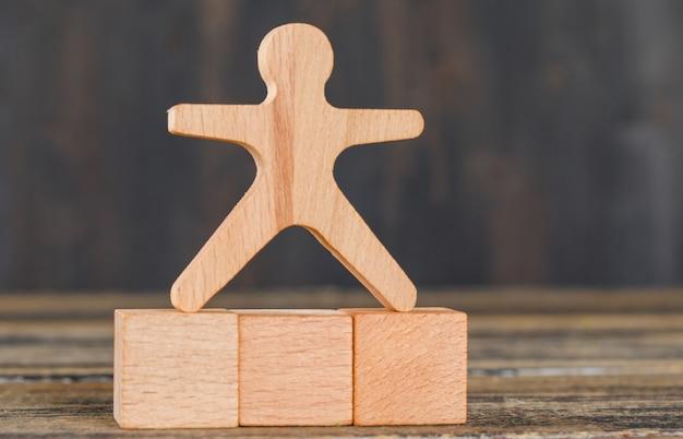 Concetto di successo di affari con il modello umano sui cubi di legno sulla vista laterale della tavola di legno.