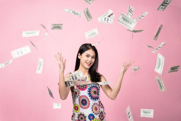 Concetto di successo, ritratto di giovane donna con le banconote in dollari che cadono nell'ia