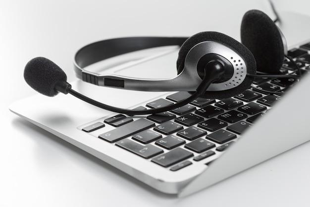 Concetto di supporto del call center. cuffia avricolare sul computer portatile della tastiera