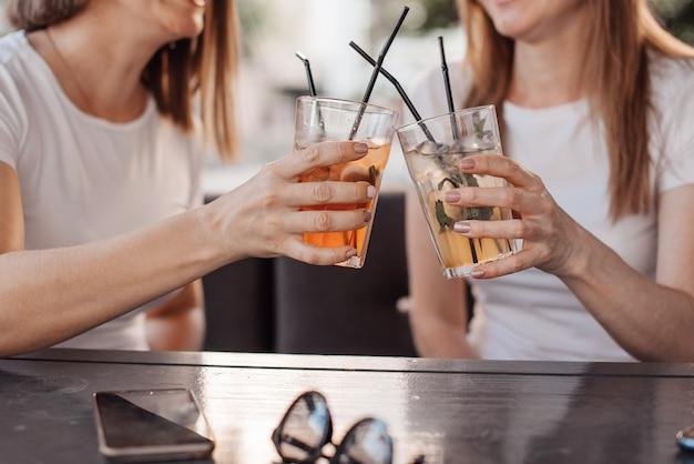 Concetto di svago, di feste, di cibo, della gente e dell'alimento - amici felici cenando al ricevimento all'aperto di estate e bevande tintinnanti