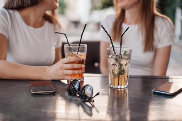 Concetto di svago, di feste, di cibo, della gente e dell'alimento - amici felici cenando alla festa in giardino dell'estate e bevande clinking