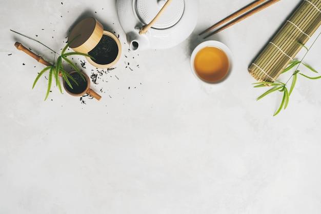 Concetto di tè asiatico, due tazze bianche di tè, teiera, set da tè, bacchette, stuoia di bambù circondato con tè verde secco su sfondo bianco