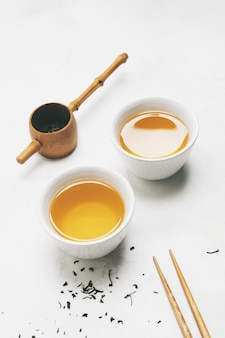 Concetto di tè asiatico, due tazze bianche di tè, teiera, set da tè, bacchette, stuoia di bambù circondato da tè verde secco