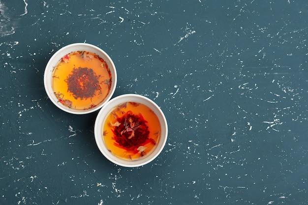Concetto di tè. diversi tipi di tè secco in ciotole di ceramica e tazze di tè aromatico