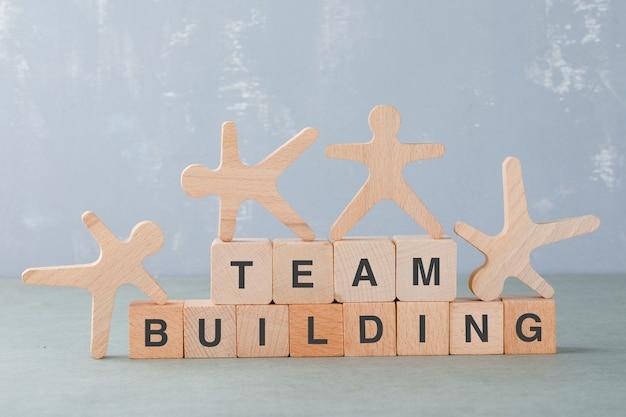 Concetto di team building con blocchi di legno, figure umane in legno su di esso vista laterale.