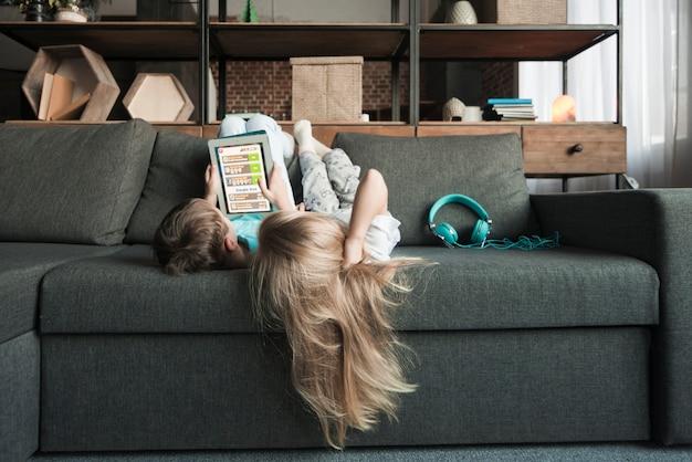 Concetto di tecnologia con ragazza sdraiata sul divano