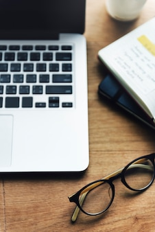 Concetto di tecnologia del posto di lavoro della tavola di legno dell'ufficio del computer portatile