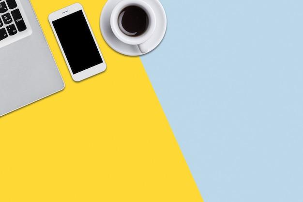 Concetto di tecnologie moderne. computer portatile, smart phone con schermo vuoto e tazza di caffè gustoso caldo sdraiato su sfondo colorato