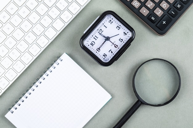 Concetto di tempo e denaro con tastiera, calcolatrice, lente d'ingrandimento, taccuino, orologio sulla vista superiore del fondo di verde navy. immagine orizzontale