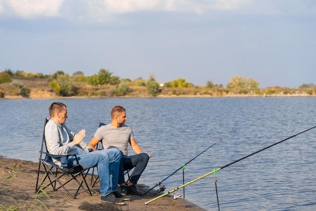 Concetto di tempo libero e persone. amici felici con canne da pesca sul molo sul lago.