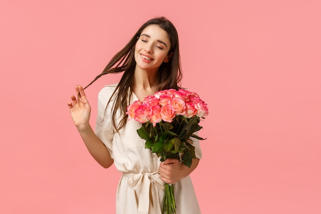 Concetto di tenerezza, delizia e san valentino. donna castana affascinante, adorabile e sensuale in vestito, arrotolando il ricciolo sui capelli chiudendo felicemente gli occhi e sognando, ricevere la consegna di fiori, tenere le rose