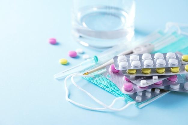 Concetto di terapia, prevenzione dell'influenza virale, attacco virale, pillole per il raffreddore, antibiotici e vitamine, maschere protettive mediche su sfondo blu. coronavirus (covid-19. copia spazio
