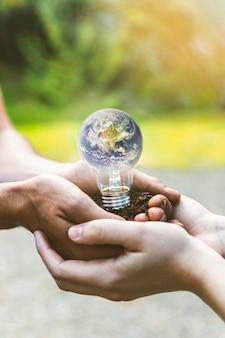 Concetto di terra all'interno della lampadina nelle mani
