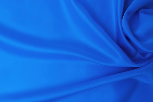 Concetto di tessuto e trama di colore blu classico alla moda. campione di tessuto di seta ondulato di colore blu classico - primo piano.