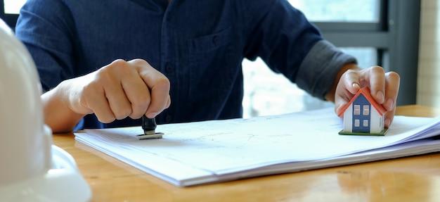 Concetto di trading immobiliare, personale in possesso di un timbro di gomma a portata di mano per approvare le vendite.