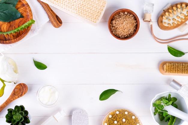 Concetto di trattamento della stazione termale con le foglie verdi, i prodotti cosmetici naturali e la spazzola di massaggio su legno bianco