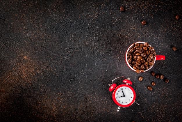 Concetto di un allegro, buon inizio di giornata, caffè mattutino. sfondo arrugginito scuro con chicchi di caffè, una sveglia e una tazza di caffè. vista dall'alto copia spazio