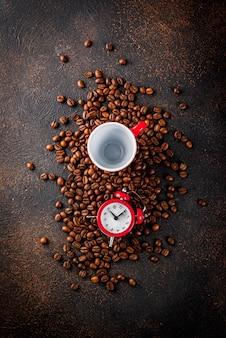 Concetto di un buon inizio allegro per il caffè del mattino. sfondo arrugginito scuro con chicchi di caffè, una sveglia e una tazza di caffè.