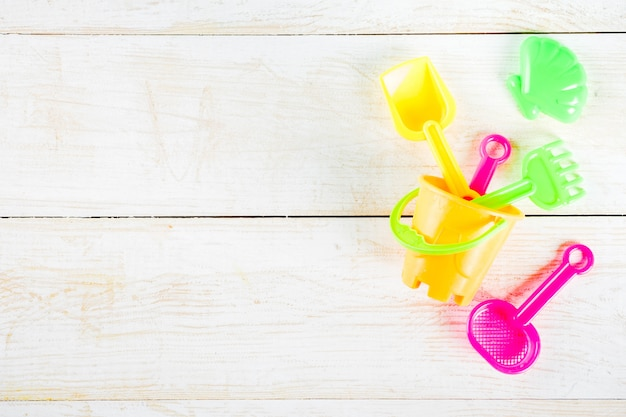 Concetto di vacanza con giocattoli da spiaggia in plastica per bambini - secchiello, paletta, rastrello, stampi barca, giocattoli salvagente