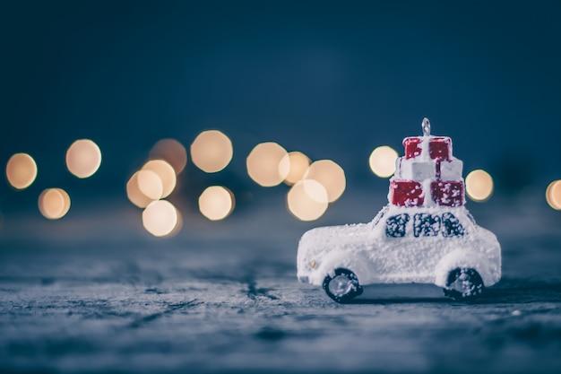Concetto di vacanza di natale con auto giocattolo e bokeh magia. copia spazio sfondo astratto