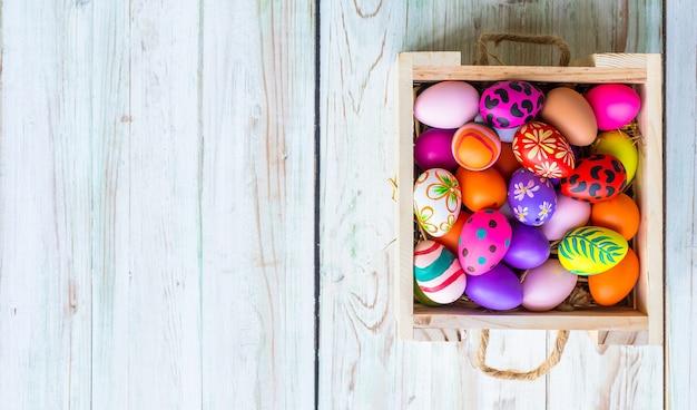 Concetto di vacanza di pasqua, merce nel cestino delle uova di pasqua colorate su fondo di legno rustico di colore pastello bianco con spazio.