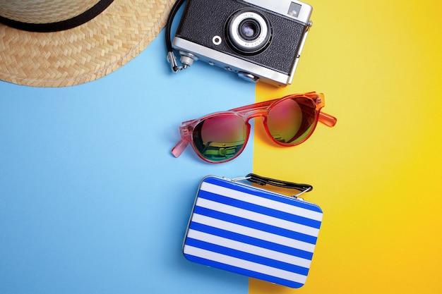 Concetto di vacanza estiva, concetto di viaggio con borsa, macchina fotografica e cappello su sfondo blu e giallo. lay piatto