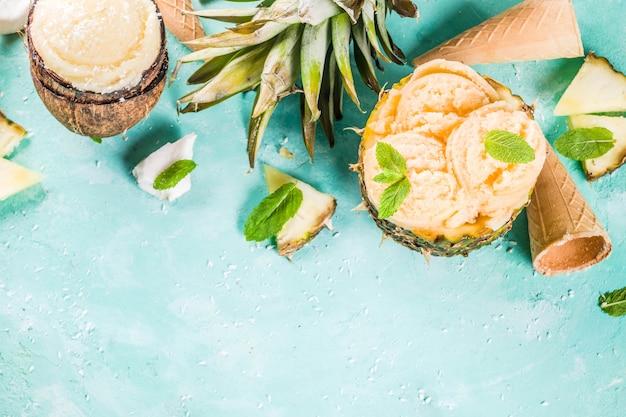 Concetto di vacanza estiva, impostare vari sorbetti di gelato tropicale, succhi di frutta congelati in ananas, pompelmo e cocco, cemento azzurro