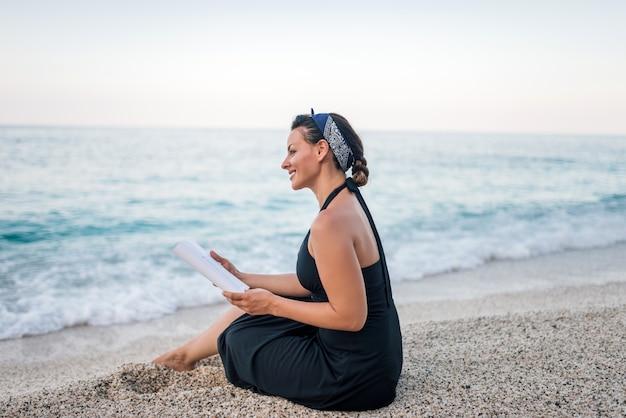 Concetto di vacanza estiva leggendo un libro sulla spiaggia.