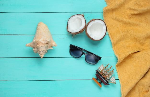 Concetto di vacanza tropicale minimalista. metà della noce di cocco, accessori da spiaggia, asciugamano su un fondo di legno blu. vista dall'alto