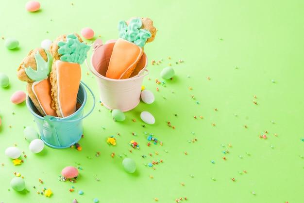 Concetto di vacanze di pasqua, biscotti dolci a forma di carote, con zuccherini dolci e caramelle all'uovo, sfondo verde chiaro copia spazio vista dall'alto, sfondo di auguri