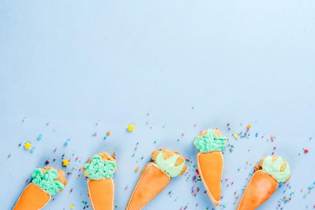 Concetto di vacanze di pasqua, biscotti dolci a forma di carote, coniglietto di pasqua, con zuccherini dolci, sfondo azzurro copia spazio vista dall'alto, sfondo di auguri