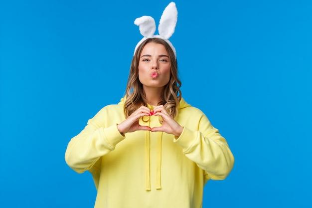 Concetto di vacanze, tradizioni e celebrazione ragazza bionda sciocca divertente e carina in felpa con cappuccio gialla e orecchie di coniglio che mostrano il gesto del cuore, fanno mwah bacio espressione, diffondono amore e positività
