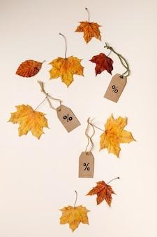 Concetto di vendita autunnale. etichette di cartone con percentuali, varietà di foglie autunnali gialle sulla superficie beige. lay piatto.
