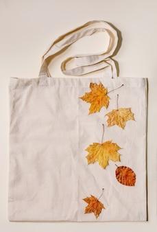 Concetto di vendita autunnale. etichette in cartone con percentuali, foglie autunnali gialle su shopping bag in lino ecologico su superficie beige. lay piatto.