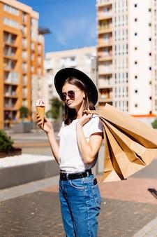 Concetto di vendita, consumismo, estate e persone. giovane donna felice con i sacchetti della spesa e il gelato sulla via della città