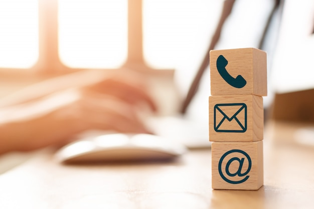 Concetto di vendita del email, mano facendo uso del computer che invia messaggio con il blocchetto del cubo di legno con l'indirizzo di posta dell'icona e il simbolo del telefono