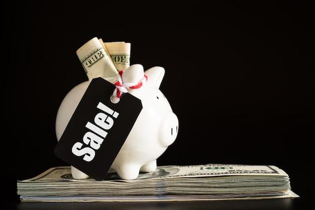 Concetto di vendita di acquisto con l'etichetta di vendita del biglietto che appende con il porcellino salvadanaio sulla pila di banconote