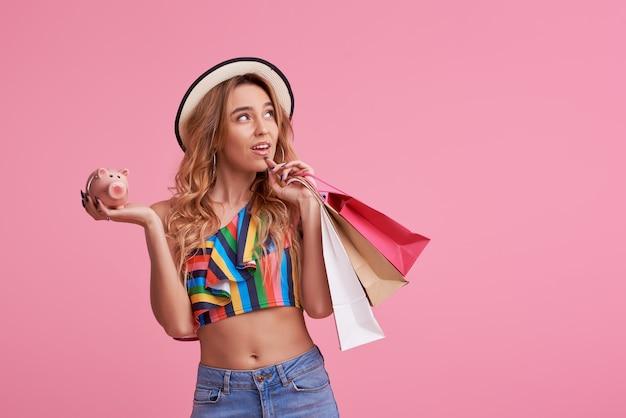 Concetto di vendita. ritratto di una bella ragazza felice in elegante cappello tenendo le borse della spesa e salvadanaio.