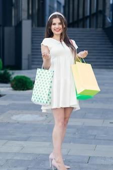 Concetto di vendita, sconto, turismo e vacanze. sorridente giovane donna in abito con borse della spesa.