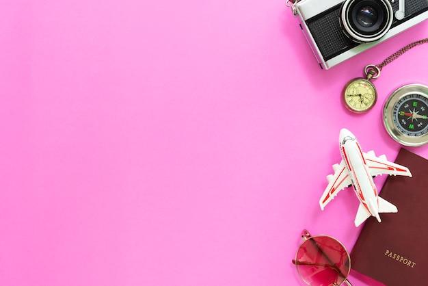 Concetto di viaggi ed orari estivi. disposizione piana degli accessori e macchina fotografica su fondo rosa.