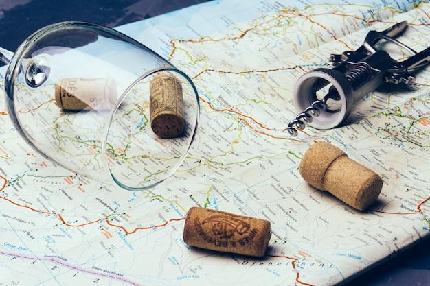 Concetto di viaggio del vino (itinerario). tappi per vino usati con un bicchiere di vino su una mappa di viaggio