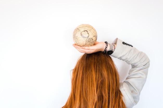 Concetto di viaggio di avventura di fine settimana estivo di viaggio di vacanza. ragazza rossa dei capelli che tiene globo antico d'annata isolato su fondo bianco. copia spazio. mock up per agenzia di turismo. idea di educazione e scoperta