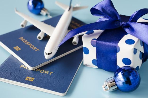 Concetto di viaggio di natale o capodanno. aeroplanino giocattolo con passaporti e confezione regalo