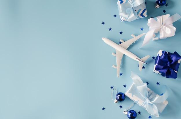 Concetto di viaggio di natale o capodanno. giochi l'aeroplano con i passaporti e i contenitori di regalo su fondo blu.