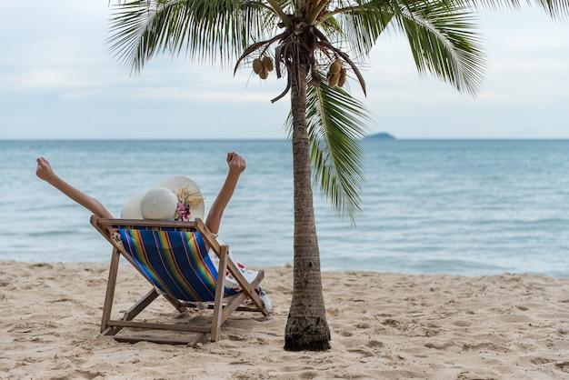 Concetto di viaggio di vacanze di vacanza della spiaggia di estate, giovane donna asiatica felice con il cappello che si rilassa sulla sedia di spiaggia e mani sollevate su.